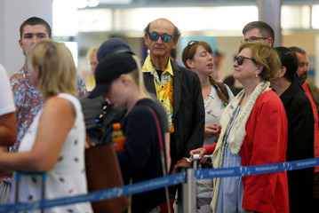 Thomas Cook passengers queue up in a check-in service at Malta International Airport