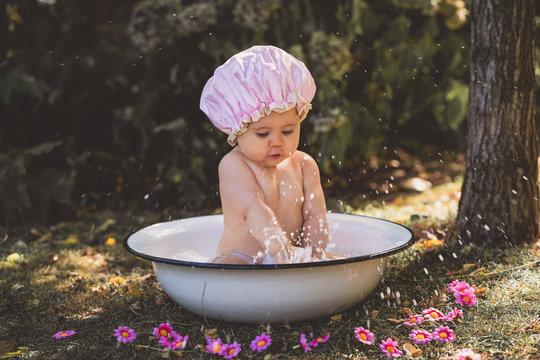 Baby kleines Mädchen Kind sitzt in Emaillle Badewanne planschen im Garten rosa Badehaube lacht Sommer vintage