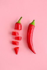 Cut and whole chili peppers on color background