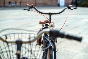Black bike mounted on a bicycle stand on italian street.
