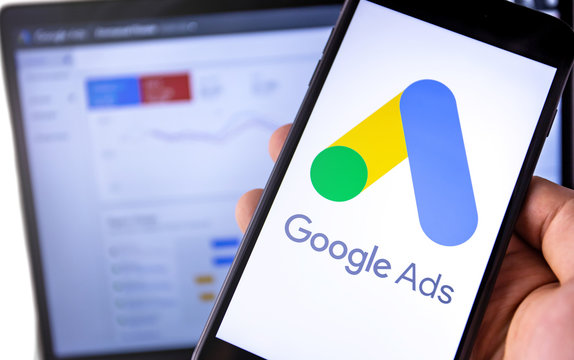 smartphone with Google Ads on the screen and display notebook background. Ads is a service of contextual, basically, search advertising from Google. Moscow, Russia - August 25, 2019