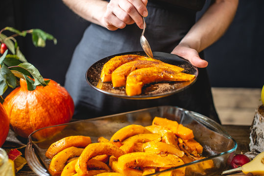 Woman chef holding slices of baked orange pumpkin with honey and cinnamon. Autumn food in a cozy kitchen. Close up