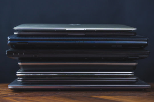 Stack of old laptops with dark background. Front