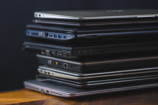 Stack of old laptops with dark background