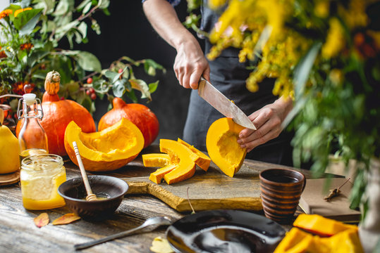 Woman cook cuts an orange pumpkin with a knife into slices for baking. Concept autumn food in a cozy dark kitchen