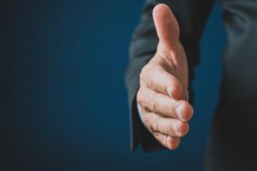 Hand of a businessman reaching in handshake