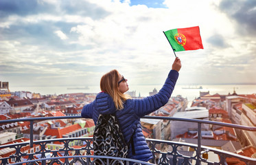 Young woman tourist enjoying beautiful cityscape top view on the old town holding the flag of Portugal in hands during the sunny day in Lisbon city Fototapete