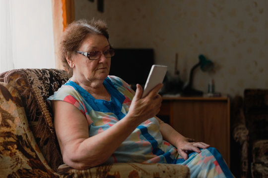 Alone elderly woman using mobile phone near the window in her living room. Internet in retirement