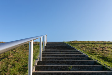 minimal background with a staircase, green grass field, and clear blue sky.