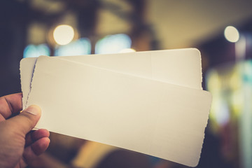 Empty paper air ticket in hand.