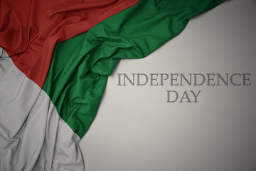 waving colorful national flag of madagascar on a gray background with text independence day.