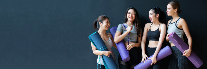 Group of women of various nationalities standing and talking about yoga And equipment is mats That which type should be chosen to buy Happily because they are healthy, strong, beautiful body.