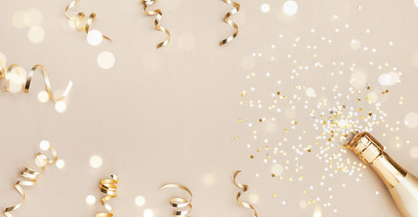 Champagne bottle with confetti stars, bokeh decoration and party streamers on golden background. Christmas, birthday or wedding concept. Flat lay.