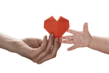 Baby to takes red paper heart from mom's hands. Concept of love, care, adoption. Color, isolated image.