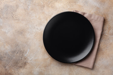 Black plate with napkin on stone table top view. Empty space for menu or recipe.