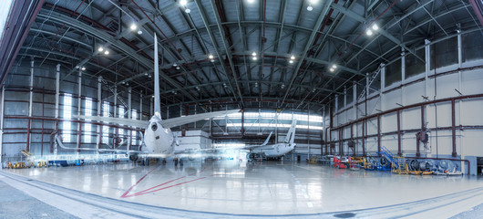 Passenger jet planes under maintenance. Checking mechanical systems for flight operations. Panorama of aircrafts in the hangar Wall mural