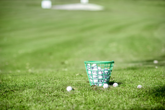 Basket full of golf balls on the playing course outdoors