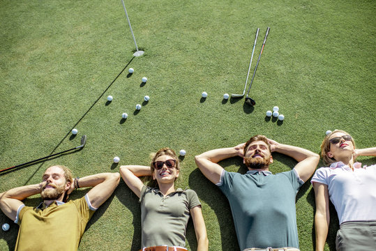 Group of a young and cheerful friends lying on the golf course with balls and putters on the grass, resting and having fun after the game