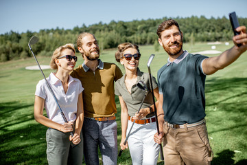 Group of young and happy friends making selfie photo while standing together with golf putters during a game on the golf course