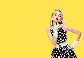 Young woman in pin up style black and white dress in polka dot, applying lipstick, isolated over yellow color background