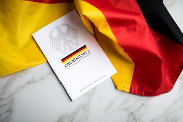 Das Grundgesetz Buch der Bundesrepublik Deutschland auf Flagge und Marmor Hintergrund