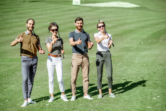 Portrait of a young group of friends as a golf team players, showing OK sign while standing together on the course outdoors