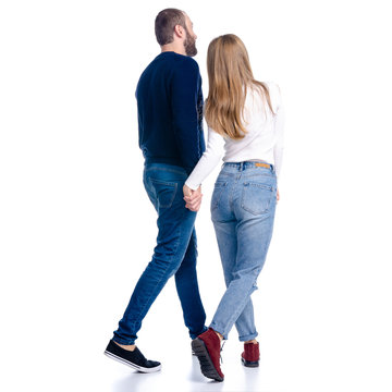Young couple woman and man walking goes looking on white background isolation, rear view