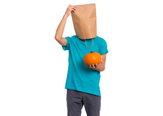 Fototapete - Happy halloween concept. Teen boy with paper bag over his head holds orange small fresh pumpkin, isolated on white background. Teenager cover head with bag. Child with food - raw vegetables in hands.