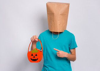 Fototapete - Happy halloween concept. Teen boy with paper bag over his head holds orange pumpkin bucket, on grey background in studio. Teenager cover head with bag, pointing finger on bucket. Child waiting candy.