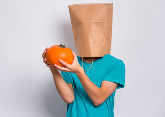Fototapete - Happy halloween concept. Teen boy with paper bag over his head holds orange small fresh pumpkin, on grey background in studio. Teenager cover head with bag. Child with food - raw vegetables in hands.