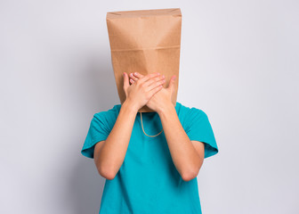 Fototapete - Portrait of teen boy with paper bag over head covers his mouth with hands. Teenager cover head with bag posing in studio. Child pulling paper bag over head. Speak no evil concept.