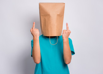 Fototapete - Portrait of teen boy with paper bag over head making middle fingers. Teenager cover head with bag showing bad gesture posing in studio. Child pulling paper bag over head doing obscene sign.