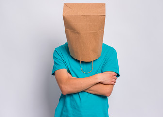 Fototapete - Portrait of offended teen boy with paper bag over head with crossed arms. Unhappy sad child pulling paper shopping bag over head, isolated on white background. Teenager folded hands in bad mood.