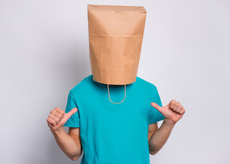 Fototapete - Portrait of teen boy with paper bag over head making thumbs up gesture. Teenager cover head with bag pointing thumbs on himself. Child pulling paper bag over head posing in studio.