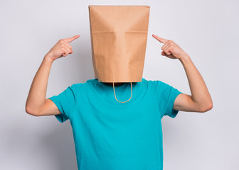 Fototapete - Portrait of teen boy show fingers paper bag over head, isolated on white background. Child pointing fingers at head with bag posing in studio. Teenager pulling paper shopping bag over head.