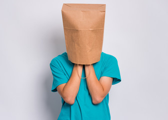 Fototapete - Unhappy teen boy with paper bag over head covering face with hands while crying. Upset teenager cover head with bag posing in studio. Child crying, not showing his tears.