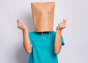 Fototapete - Teen boy with paper bag over head showing sign symbol of money by fingers, isolated on white background. Teenager cover head with bag doing rich gesture. Child gesture rubbing fingers together.