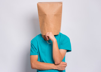 Fototapete - Pensive teen boy with paper bag over head. Thoughtful teenager cover head with bag holding hand near face posing in studio. Child pulling paper bag over head.