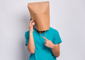 Fototapete - Teen boy with paper bag over head speaking on mobile phone, isolated on white background. Teenager cover head with shopping bag holds smart phone. Child pulling bag over head.