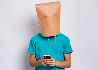 Fototapete - Teen boy with paper bag over head looking at his smart phone while text messaging, isolated on white background. Teenager cover head with shopping bag holds mobile phone. Child pulling bag over head.