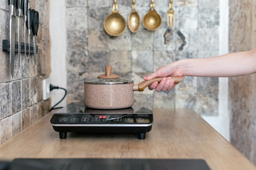 Girl cooking food in kitchen with small electric stove