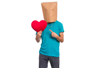 Fototapete - Valentines Day concept. Teen boy with paper bag over his head holds red heart, isolated on white background. Boy holding symbol of love, family, hope. Teenager cover head with bag posing in studio.