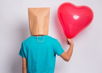 Fototapete - Back view. Valentines Day concept. Teen boy with paper bag over head holds red heart shaped balloon. Boy holding symbol of love, family, hope. Teenager cover head with bag in studio - rear view.