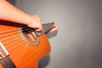 Guitar and strings, man's hand on a gray background in the studio, wide angle photo.