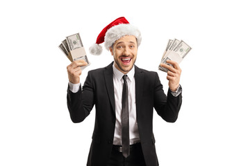 Happy man in a black suit and a Santa Claus hat holding money in both hands