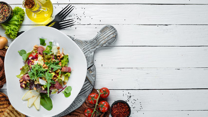 Vegetable salad with prosciutto and nuts. Food. Top view. Free space for your text.