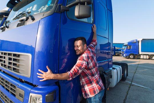 Truck driver loves his job. Professional trucker driver hugging his truck cabin loving his job.