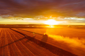 Combine harvester harvests wheat in the field at sunset in autumn in Russia. view from a height of equipment and field. Fototapete
