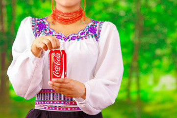 Quito, Ecuador - May 06, 2017: Young woman wearing an indigenous clothes and pointing in from of her a coke while she is open it, in a forest background
