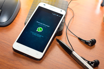 QUITO, ECUADOR - AUGUST 3, 2015: White smartphone lying on wooden desk with WhatsApp website screen next to a pen, headphones and mouse, business communication concept